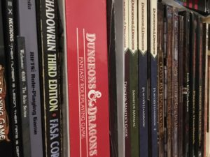 A row of role-playing game books on a shelf