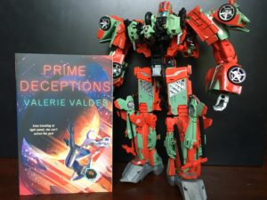 The book Prime Deceptions by Valerie Valdes next to the Victorion Transformers model
