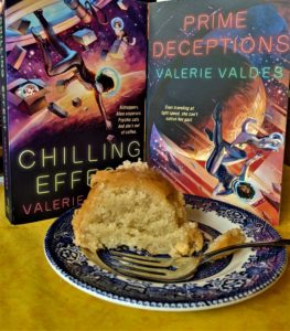 Photo of a slice of cake on a plate with a fork, with the books Chilling Effect and Prime Deceptions in the background